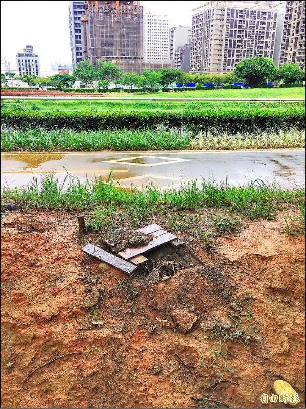 民眾PO文批評,坑洞用木板蓋住遮掩缺失,水務局允諾改善。(記者謝武雄攝)