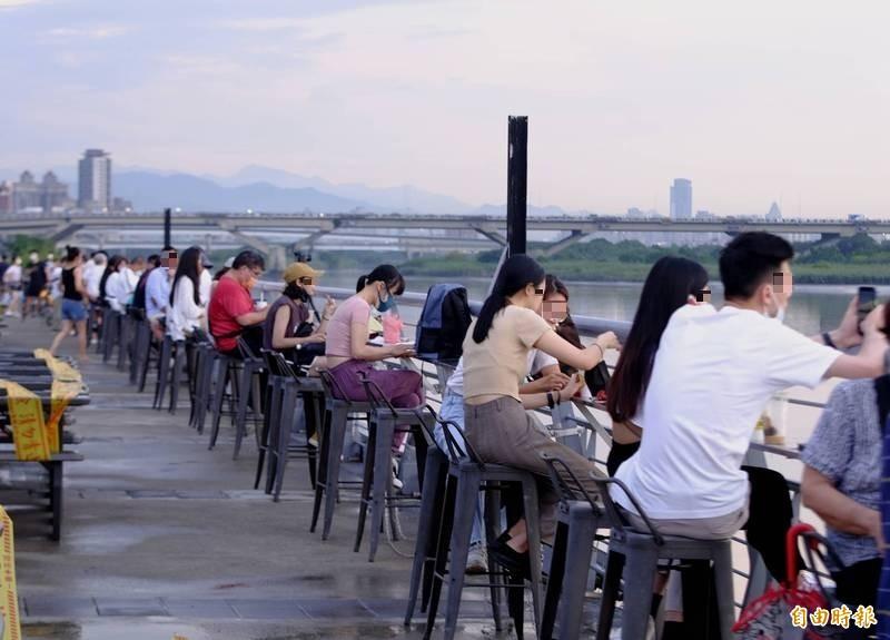 大批民眾在大稻埕碼頭買完東西,於現場脫下口罩「開吃」。(記者王藝菘攝)