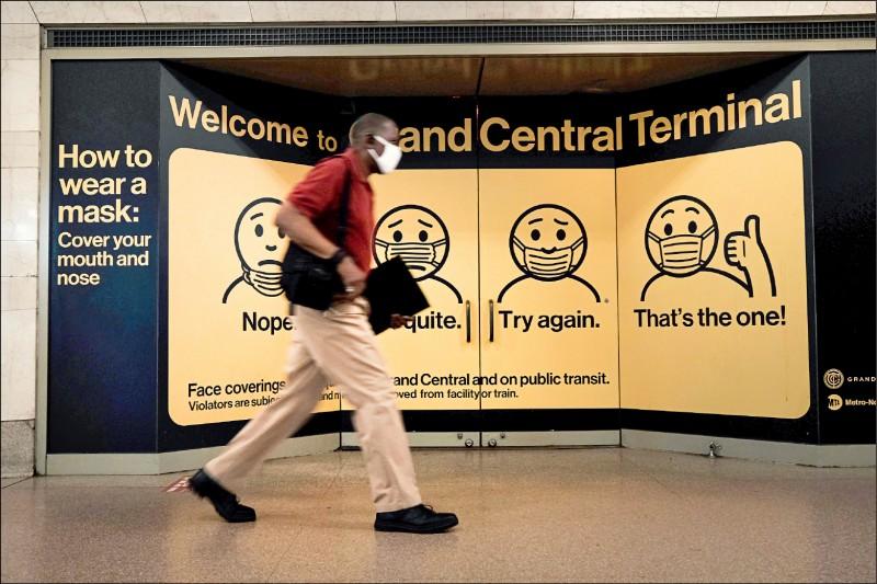 為遏止傳播速度更快的Delta變種病毒導致美國疫情升溫,美國疾病管制暨預防中心推翻稍早的防疫指引,改口建議在染疫高風險區的室內應該戴口罩。圖為紐約中央車站內一名戴著口罩的男子,二十七日行經一面教導民眾如何正確戴口罩的告示牌。 (法新社)