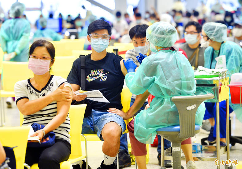 Teachers get vaccinated at a mass inoculation event at the Taipei Expo Park yesterday. Photo: Peter Lo, Taipei Times