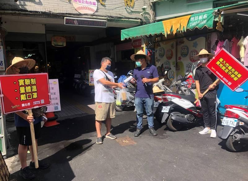 戴斗笠的年輕人組成「市場防疫宣導員」,在南屯市場入口幫買菜族噴酒精。(「南屯即時通」、記者張瑞楨翻攝)