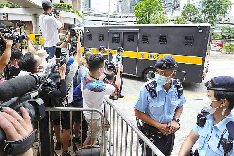 Police officers stand guard as a prison truck carrying Tong Ying-kit leaves a Hong Kong court yesterday, after his sentencing for contravening Hong Kong's National Security Law. Photo: AP