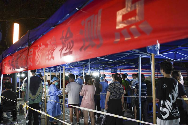 江蘇疫情持續延燒,至今累計198例本土感染者,共分布5市。圖為南京市民排隊接受檢測。(路透)