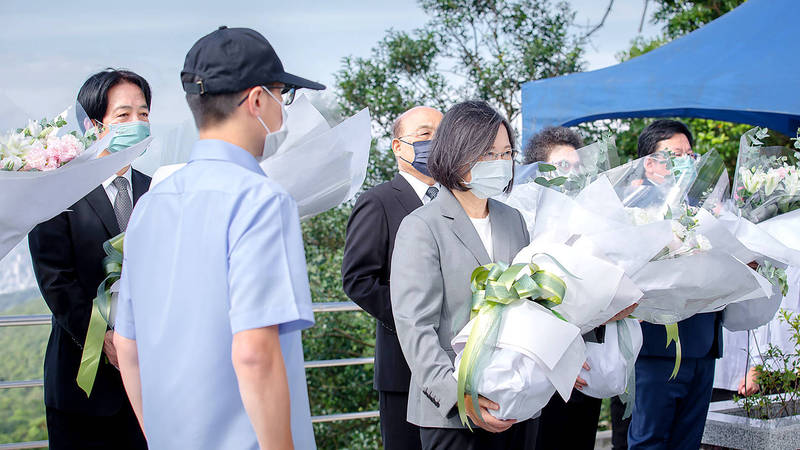 President Tsai Ing-wen, center, holds flowers as top officials, including Vice President William Lai, left, and Premier Su Tseng-chang, third left, honor former president Lee Teng-hui at the Wuzhi Mountain Military Cemetery in New Taipei City's Sijhih District on the anniversary of his passing yesterday. Photo provided by the Presidential Office via CNA
