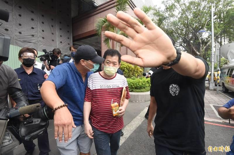 北檢諭令「美鷹會」要角王鑫(中)200萬元交保,並限制出境出海。(記者劉信德攝)