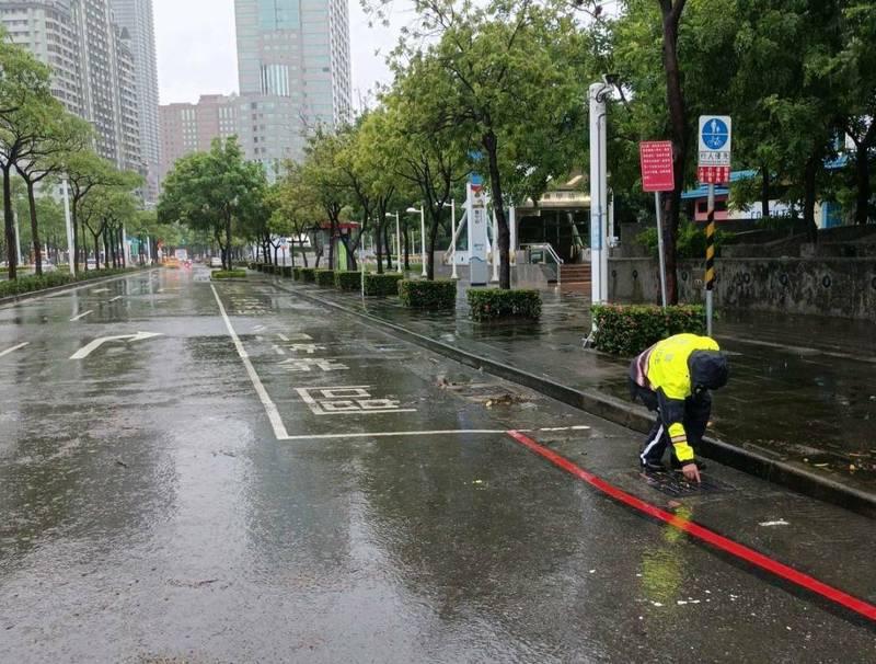 積水隨雨勢轉小很快消退,員警也順手清理排水空上的落葉等。(民眾提供)