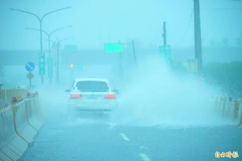 林邊台17線磘仔口橋路車輛行經時激起大量水花。(記者陳彥廷攝)