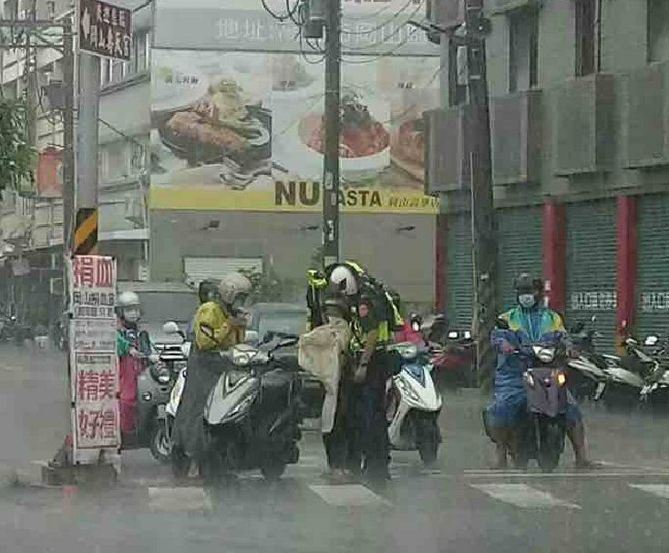 警員徐敏翔(中)脫雨衣幫老夫妻擋雨。(岡山警分局提供,取自臉書「岡山人」社團)