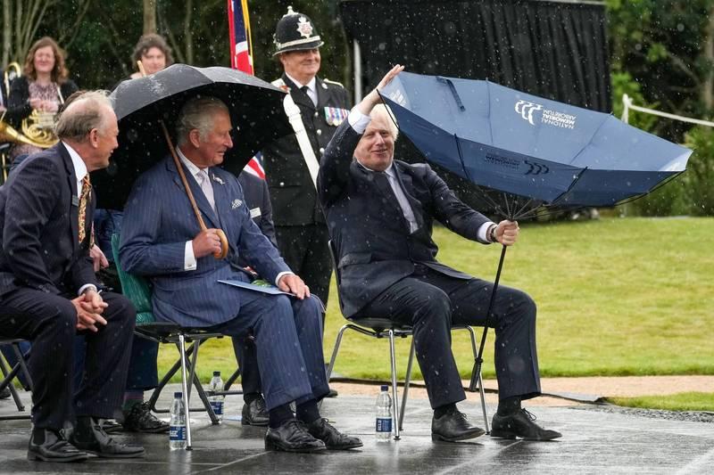 英國首相強森在活動中因一把雨傘鬧出笑話。(路透)
