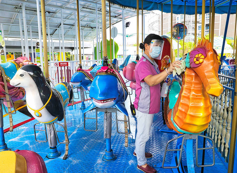 A worker at the Taipei Children's Amusement Park in Shilin District yesterday disinfects a carousel in preparation for today's conditional reopening. Photo: CNA
