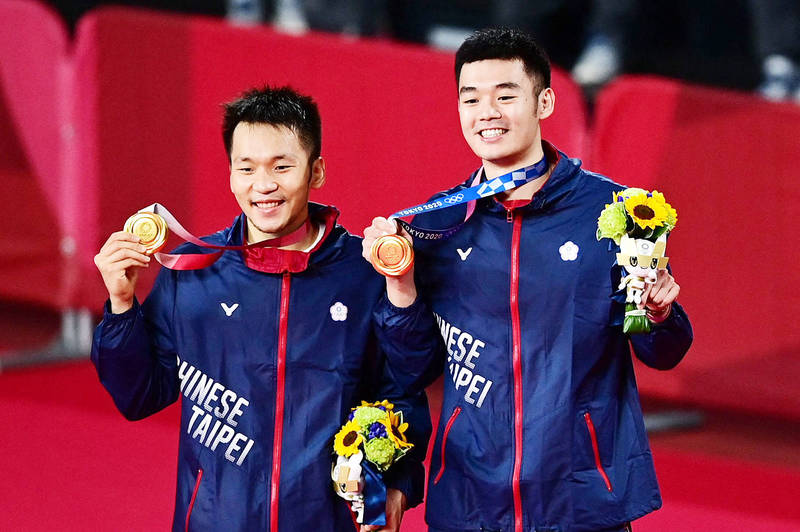 Taiwan's Lee Yang, left, and Wang Chi-lin pose with their men's doubles badminton gold medals at a ceremony at the Musashino Forest Sports Plaza in Tokyo yesterday. Photo: AFP