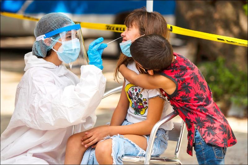 刊登在《细胞(Cell)》期刊的美国最新研究显示,鼻咽做为人体面对武汉肺炎病毒入侵的第一「战场」,其第一时间反应和染疫者症状轻重明显相关。轻、中度患者鼻咽上皮细胞和抗病毒反应有关的基因活化增加,尤其是受第一型干扰素(IFN-I)活化的干扰素刺激基因(ISGs)。反观重症患者抗病毒反应则「迟钝」,对干扰素也反应很小,以致病毒更容易进入上、下唿吸道。图为乌拉圭首都蒙德维的亚卫生照护人员从一名女孩的鼻部採取样本。(美联社档案照)(photo:LTN)