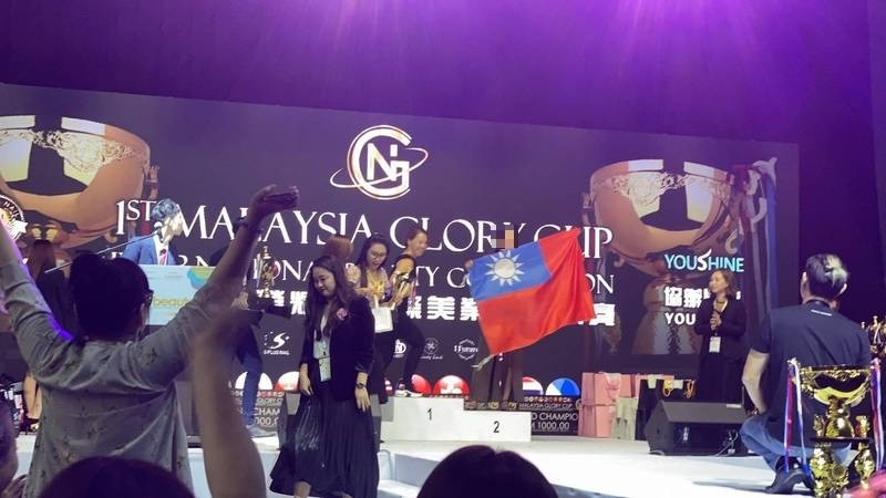 去年她代表台灣獲獎時,她展開國旗受獎。(李女提供)