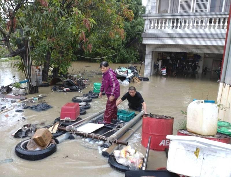 關廟下起豪雨,南雄橋旁住戶嚴重淹水,居民搭自製膠筏送飯。(民眾提供)