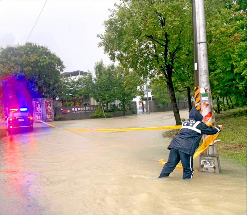 高市岡山區本工西路與本工一路口積淹水,警方現場拉起封鎖線,提醒民眾改道通行。(民眾提供)