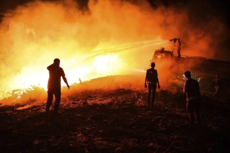 土耳其安塔利亞省馬納夫加特市的警察與當地居民試圖控制火勢。(美聯社)