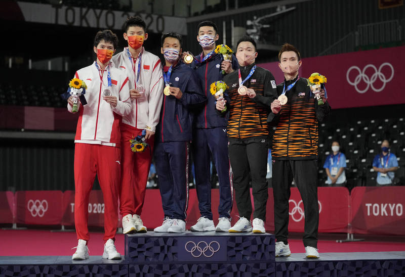 台灣羽球男雙王齊麟、李洋7月31日在東京奧運,拿下我國羽壇奧運史上首面金牌,頒獎時李洋還邀請中國選手一起上台合影留念。(歐新社)