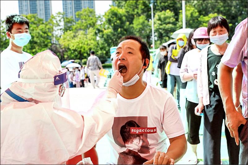 從南京祿口機場引爆的新一波武漢肺炎疫情,正在中國擴散。圖為與南京同屬江蘇省的淮安市,居民七月三十日排隊接受核酸檢測。(法新社)