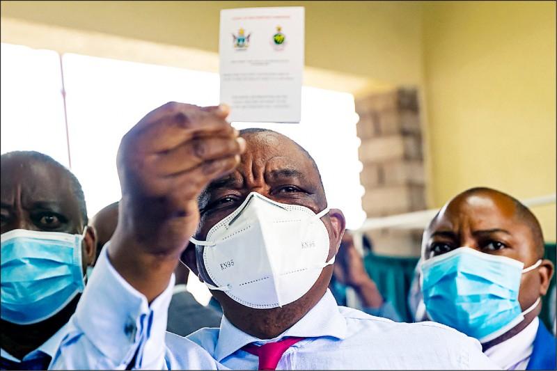 辛巴威副總統奇溫加到中國就醫,隨行官員確診武漢肺炎。圖為奇溫加今年二月在辛國接種中國「國藥」疫苗,高舉自己的疫苗接種紀錄卡供媒體拍攝。(法新社檔案照)