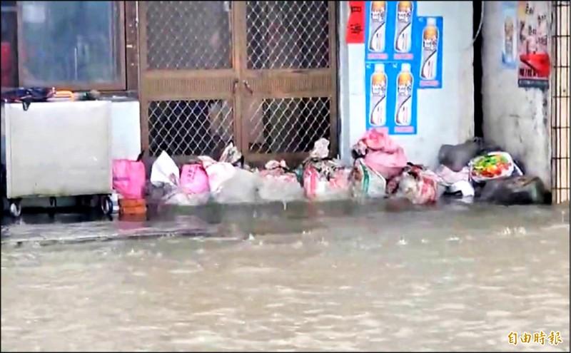 民眾在大門口堆起沙包以防止積水侵入家中。(記者葉永騫攝)