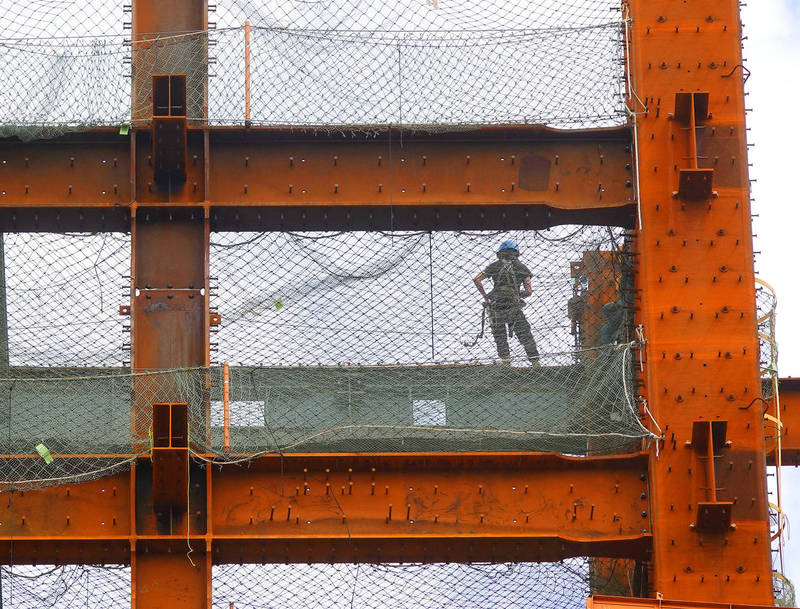 A worker stands on a steel beam at a construction site in Taipei yesterday. Photo: CNA