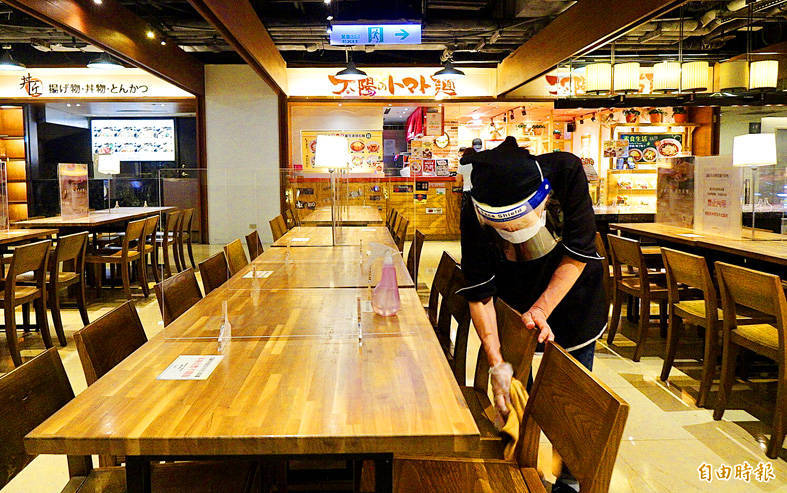 An employee disinfects seating at a food court in New Taipei City yesterday. Photo: Peter Lo, Taipei Times