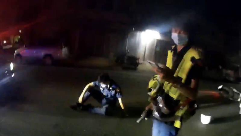 頭城分駐所警員蔡旻庭中彈後壓制嫌犯,等候其他警力前來支援;其他警察接手後,蔡痛苦坐在地上等候救護車。(記者蔡昀容翻攝)