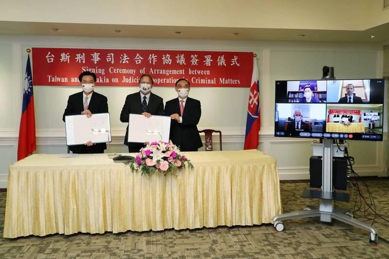 外交部長吳釗燮(左)、斯洛伐克駐台代表博塔文(中)及法務部長蔡清祥(右)手持簽署完成的協議,與線上觀禮的斯洛伐克政要及我駐斯洛伐克代表李南陽合影。(外交部提供)