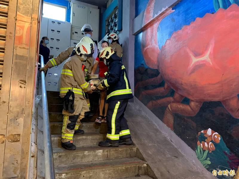 消防隊員合力將絞肉機緩慢抬下樓,避免傷者傷勢擴大。(記者吳昇儒攝)