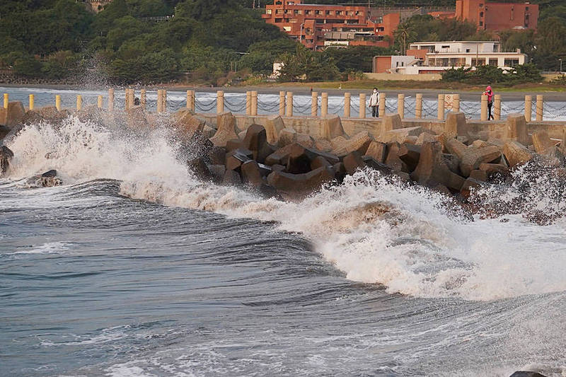 People watch as waves break against a pier in Kaohsiung yesterday. Photo: CNA