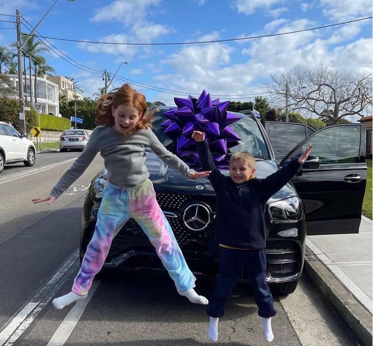 澳洲名媛賈琴科買了一輛全新賓士車送9歲女兒琵西(左),琵西和弟弟杭特(右)開心的在車前跳起來。(圖翻攝自@pixiecurtis_IG)