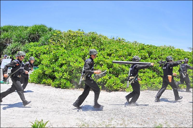 因應敵情威脅,駐守東沙島的海巡署官兵,將於九月五日、十二日進行季度「對海實彈射擊」演訓,包括「紅隼」反裝甲火箭彈等,預料都將納入操演軍備之列。圖為二○一二年五月立委考察東沙戰備演練,海巡官兵扛起八一公厘迫擊砲快跑前進。(中央社資料照)