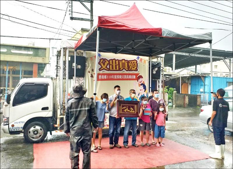 里港鄉公所在風雨中出動行動舞台車表揚模範父親,工作人員還幫撐棚子防淋雨。(屏東縣里港鄉公所提供)
