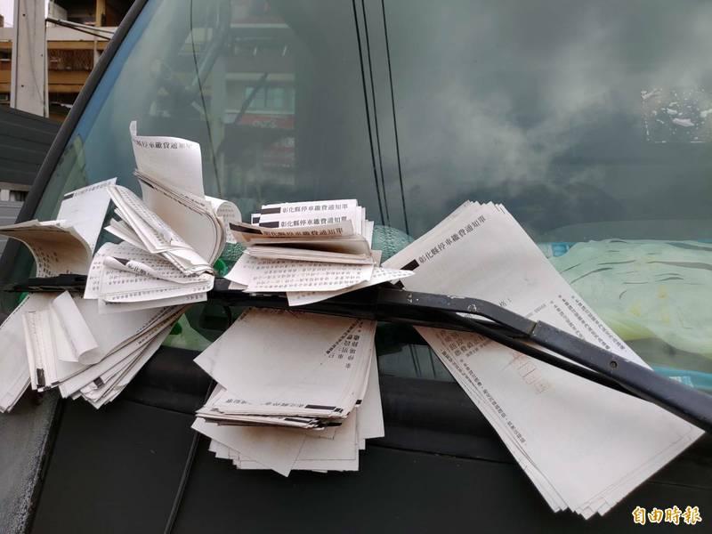 彰化市中正路的收費停車格上,赫然可見車子雨刷上夾滿了停車單。(記者劉曉欣攝)
