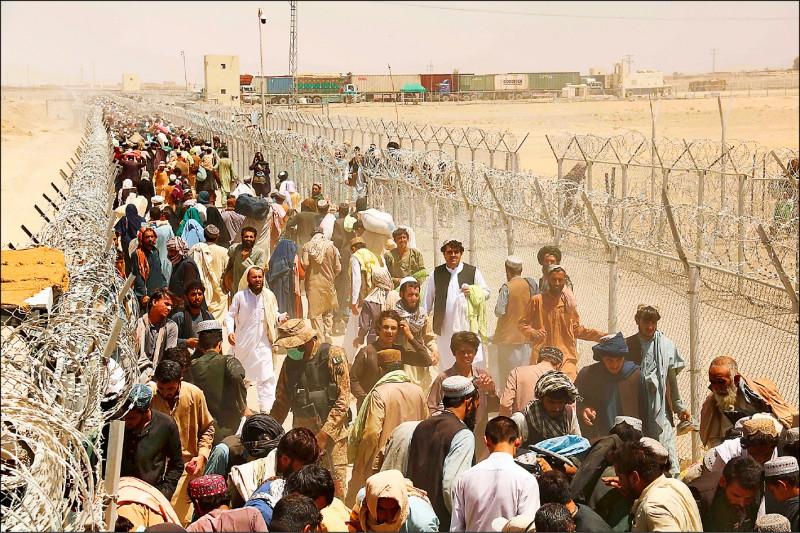 阿富汗戰局急轉直下,許多人民急忙逃往鄰國。圖為巴基斯坦13日重新開放毗鄰阿國的城鎮杰曼(Chaman),許多人等著通行。(歐新社)