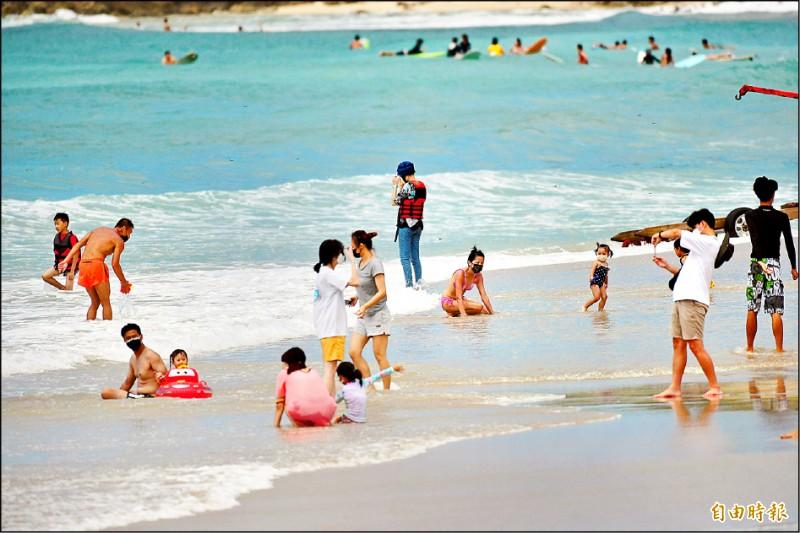 海邊戴口罩進行水上活動畫面,也成為疫情警戒降級後的特殊景象。(記者蔡宗憲攝)