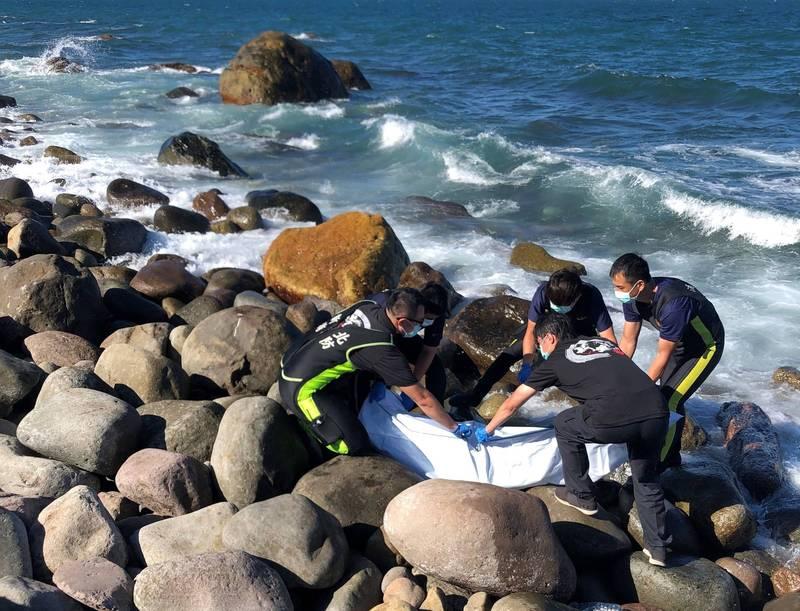 消防隊員將遺體打撈上岸,並裝進屍袋,後續將交由轄區警員及海巡隊員進一步調查。(記者吳昇儒翻攝)