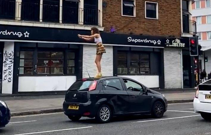 英國1名女子隨機爬上汽車車頂熱舞,慘遭車主擊落。(圖擷取自Twitter/@AminNumeroUno)