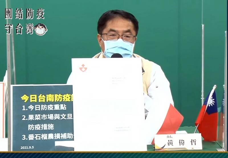 台南市長黃偉哲在南市府防疫記者會上,特別在桌上豎立台灣和波蘭兩國的國旗,感謝波蘭贈我疫苗。(擷取自南市府線上防疫記者會)