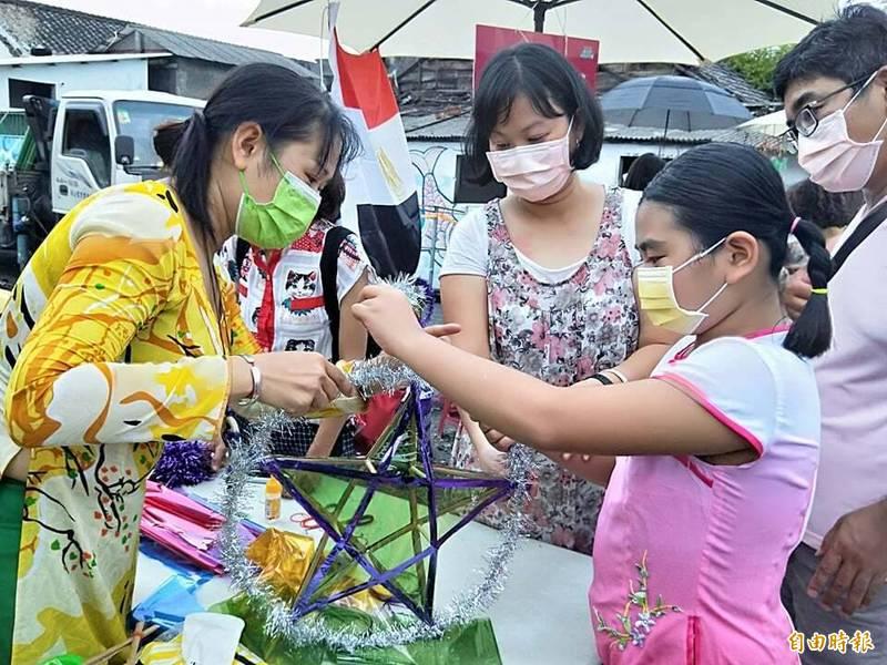 屏東多元文化創意市集今天是首度走出屏東市,來到潮州日式文化園區舉辦,朱麗鶯(黃衣者)指導親子製作越南的星星燈籠。(記者陳彥廷攝)