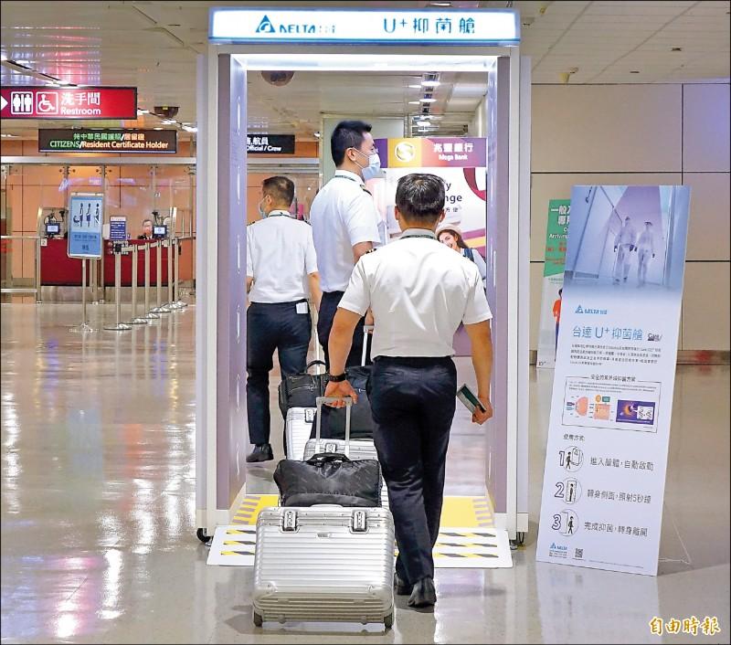 長榮航空有三位機師接連確診,長榮航空全面普篩。圖為長榮航空機師昨入境時,利用抑菌艙加強全身消毒。(記者朱沛雄攝)