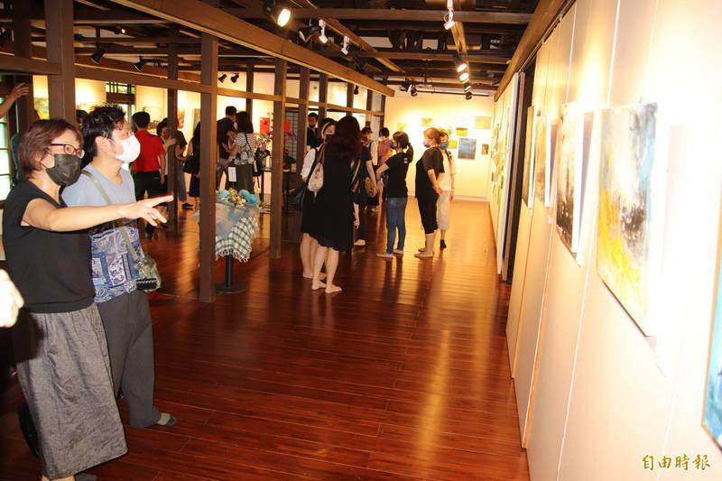 業餘畫家郭秋燕(左舉手者)跟來訪欣賞創作的同好們分享她每幅畫作的創作緣由。(記者黃美珠攝)