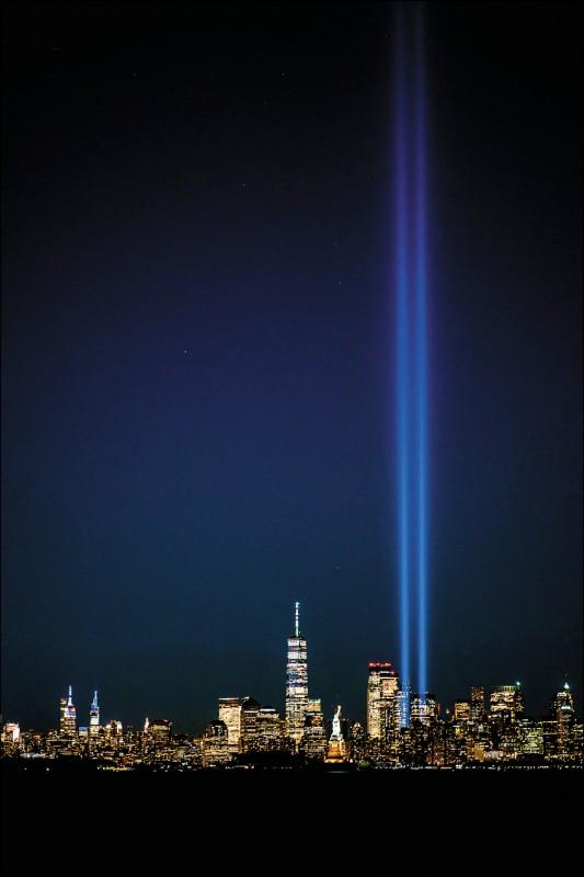 美國紐約市曼哈頓的天際線在911恐怖攻擊20週年前夕的10日晚間,出現兩道打向天空、代表在911恐攻中遭客機撞擊後坍塌的世貿中心雙塔的光束。(路透)