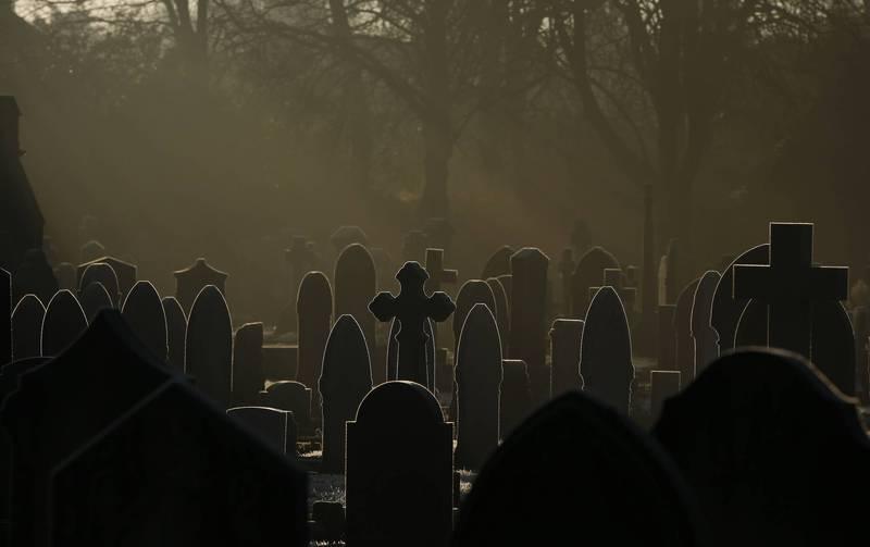 英國1名女子打扮成修女在墓園內與骷髏頭共舞。墓園示意圖。(路透)