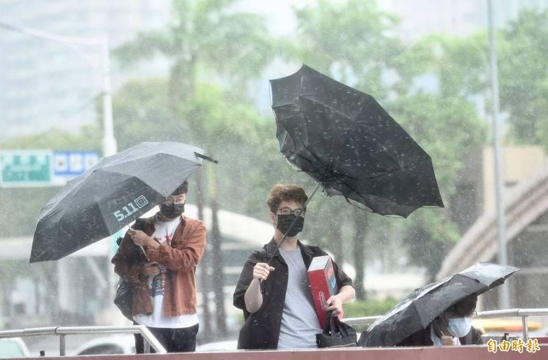 璨樹(CHANTHU)颱風持續往北移動,今天下午3點時的中心位置在北緯25.4度,東經122.4度,即在台北的東北東方約100公里之海面上。圖為外出民眾在強風中寸步難行。(記者羅沛德攝)