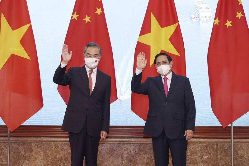 中國外長王毅(左)在9月11日與越南總理范明政(右)會談。(美聯)