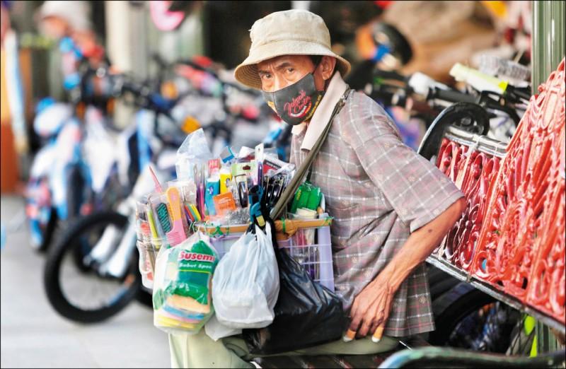 東南亞各國疫情燃燒,但封鎖措施重創經濟,在防疫與民生之間求取平衡,各國選擇解封,重新開放經濟活動。圖為印尼茂物市一名街頭小販在等候顧客青睞。(歐新社)