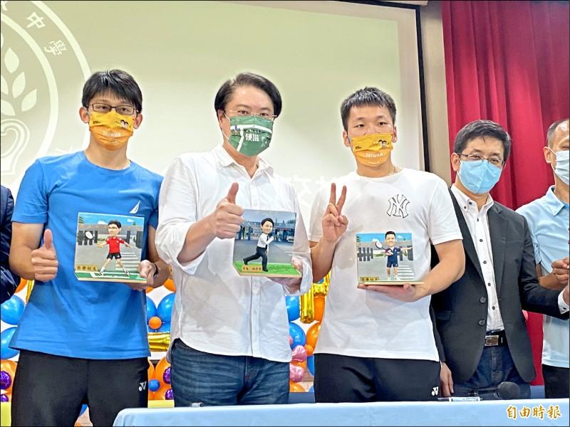 在東京奧運男子羽球雙打賽勇奪金牌的選手李洋(左三)與教練陳宏麟(左一)重返母校基隆高中,與基隆市長林右昌(左二)一起展示校方準備好的可愛公仔。(記者俞肇福攝)