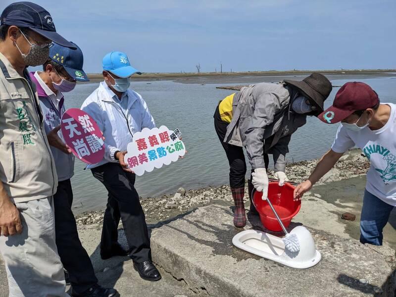 嘉義縣環保局到白水湖壽島的馬桶頒發「特優之榮譽公廁」。(嘉義縣府提供)