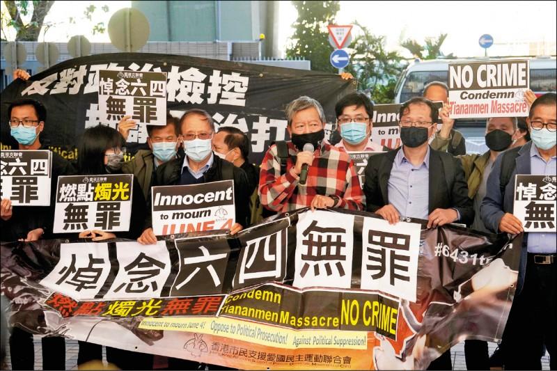 十二名香港民主派人士十五日因「煽惑他人參與未經批准集結」與「明知而參與未經批准集結」罪,被法院判刑四個月至十個月不等,其中三人獲判緩刑。圖為今年二月香港民主派人士在法院外舉起「悼念六四無罪」布條。(美聯社檔案照)